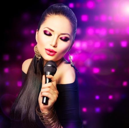 Hermosa muchacha cantante Belleza con micrófono