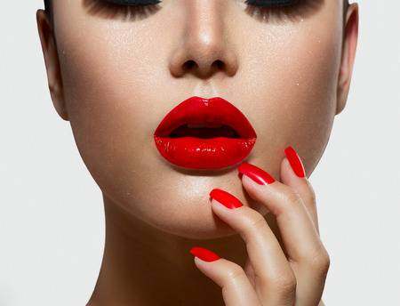 lip shine: Labbra rosse sexy e unghie primo piano manicure e trucco Archivio Fotografico