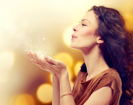 Mujer joven que sopla polvo mágico con las estrellas de las manos Foto de archivo