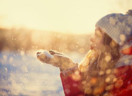 Beauty Winter meisje blazen sneeuw in ijzige winter Park Outdoors Stockfoto