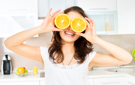 Funny Woman with Orange over Eyes in the Kitchen photo