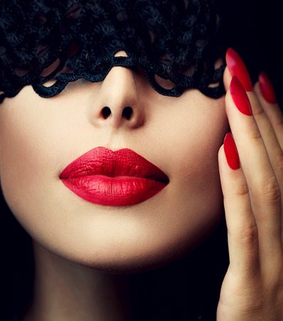 Beautiful Woman with Black Lace Mask over her Eyes Фото со стока