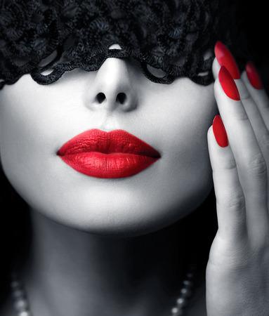 彼女の目の上の黒いレースのマスクを持つ美しい女性