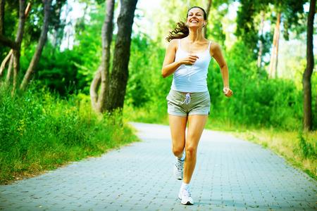 outdoor: Funcionamiento de la mujer de entrenamiento al aire libre en un parque Retrato integral Foto de archivo
