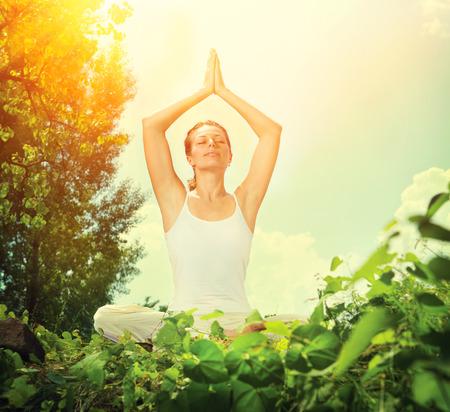 Mujer joven que hace ejercicios de yoga al aire libre