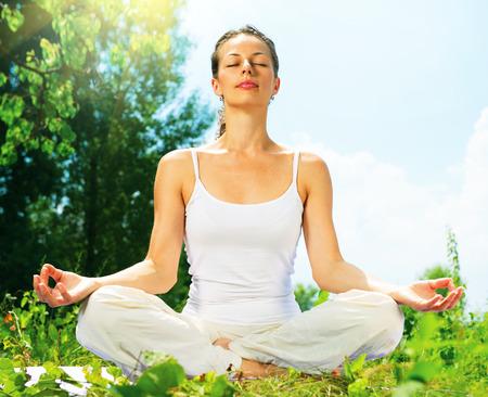 balanza: Mujer joven que hace ejercicios de yoga al aire libre