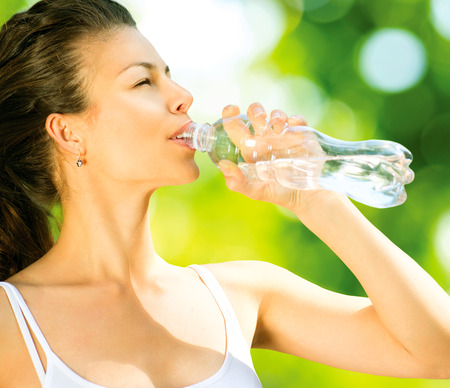 Healthy and Sporty Young Woman Drinking Water from the Bottle photo