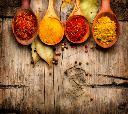 Spices and herbs  Curry, saffron, turmeric, cinnamon over wood Stock Photo