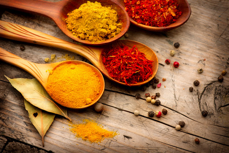 Various spices and herbs over wooden background Imagens