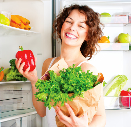 refrigerator with food: Beautiful young woman near the refrigerator with healthy food