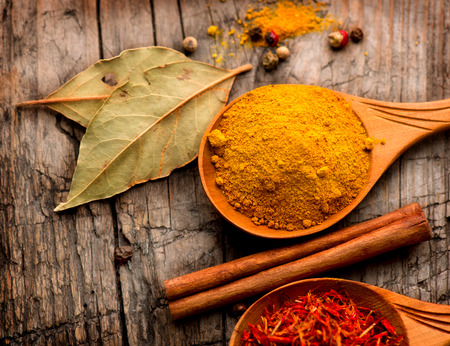 Spices and herbs  Curry, saffron, turmeric, cinnamon over wood photo