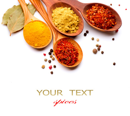 wooden spoon: Spices and herbs  Curry, saffron, turmeric, cinnamon over white