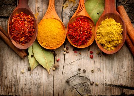 cuchara: Especias y hierbas curry, azafrán, cúrcuma, canela sobre madera