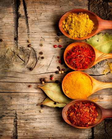 Spices and herbs  Curry, saffron, turmeric, cinnamon over wood Imagens