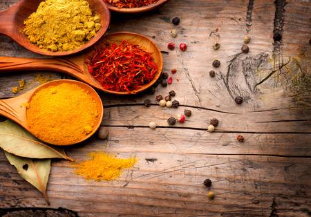 spezie: Spezie ed erbe aromatiche Curry, zafferano, curcuma, cannella su legno Archivio Fotografico
