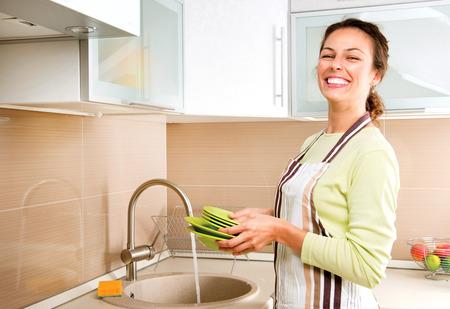 lavar: Mujer Lavar los platos de cocina Foto de archivo
