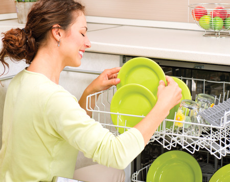 dishwasher: Dishwasher  Happy Young Woman in the Kitchen doing Housework Stock Photo