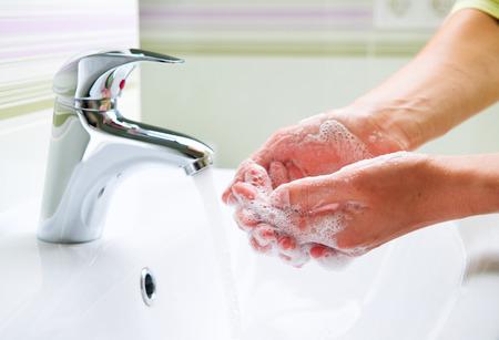 Lavarse las manos con jabón mujer de la limpieza de manos en un cuarto de baño