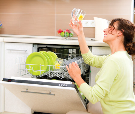 washup: Dishwasher  Happy Young Woman in the Kitchen doing Housework Stock Photo