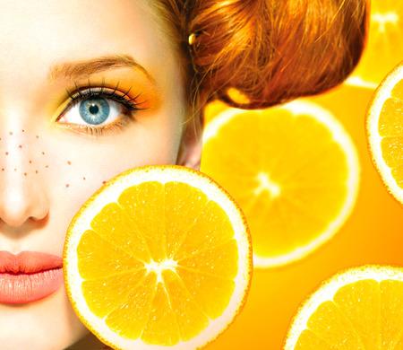 Model van de schoonheid meisje met sappige sinaasappelen Sproeten