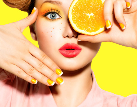 nail care: Teen girl with freckles, red hairstyle, yellow makeup and nails