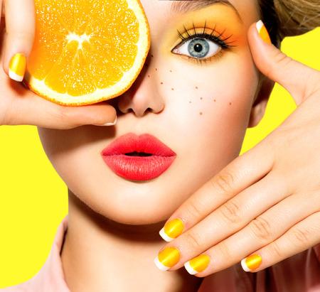 La muchacha adolescente con pecas, peinado rojo, el maquillaje y las uñas de color amarillo