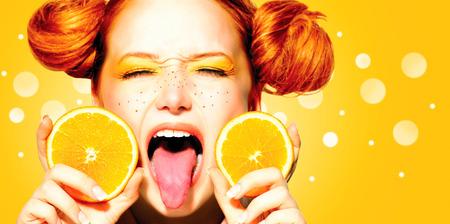 Belleza chica adolescente alegre con naranjas jugosas Pecas