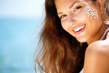 sun tan: Beauty Girl Applying Sun Tan Cream on her Face  Sun Tanning