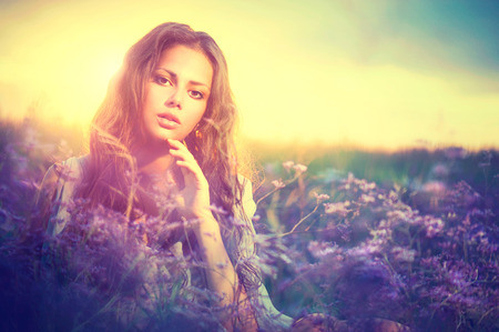 fantasy makeup: Mujer sensual que miente en un prado con flores de color violeta Foto de archivo
