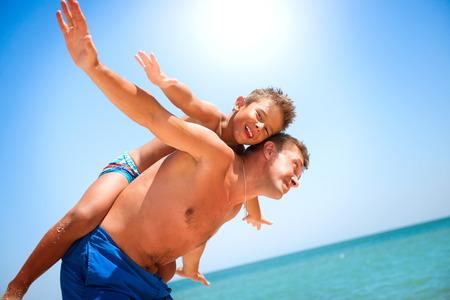 nadar: Padre e hijo se divierten en el concepto de playa de vacaciones Foto de archivo
