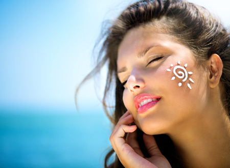 Beauty Girl Aplicando Bronceado crema en la cara Sun Tanning Foto de archivo