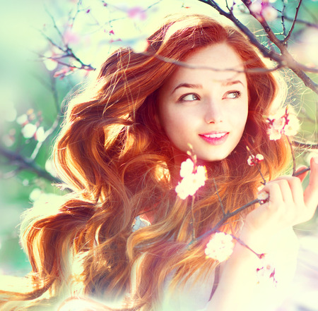 long curly hair: Spring beauty girl with long red blowing hair outdoors