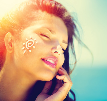 Beauty Girl Applying Sun Tan Cream on her Face  Sun Tanning Stok Fotoğraf - 27485612