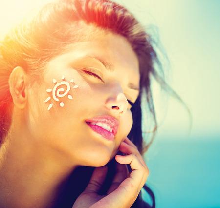 Beauty Girl Applying Sun Tan Cream on her Face  Sun Tanning photo