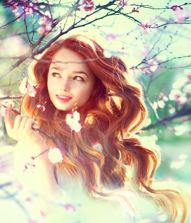 Menina da beleza da Primavera com cabelo de sopro longo vermelho ao ar livre