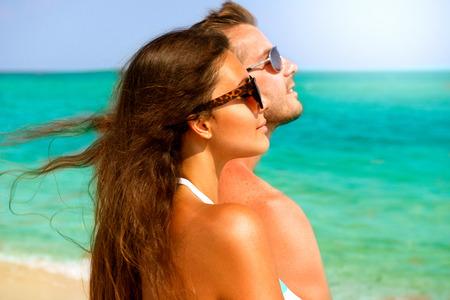 couple heureux: Couple heureux dans des lunettes de soleil en s'amusant sur la plage d'�t�