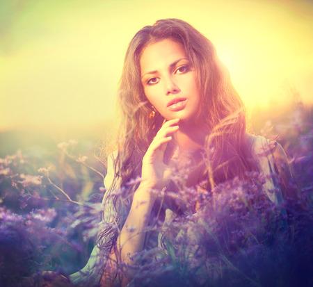 field of flower: Donna sensuale sdraiata su un prato con fiori viola