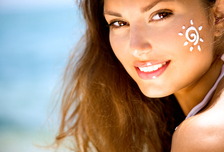 sun tanning: Beauty Girl Applying Sun Tan Cream on her Face  Sun Tanning