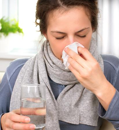 Mujer de estornudo en tejido Mujer enferma de la gripe Foto de archivo