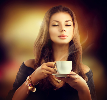 Beauty Model Girl with the Cup Tea or Coffee photo