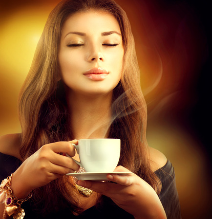 Beauty Model Girl with the Cup Tea or Coffee