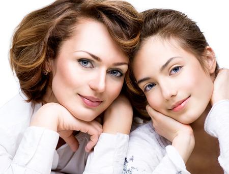Atraktivní šťastná matka a usmívající se dospívající dcera