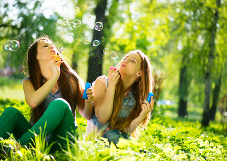 Joyful teenage girls laughing and blowing soap bubbles photo
