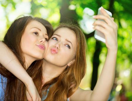 스마트 폰 Selfie와 함께 사진을 찍고 사춘기 친구 스톡 콘텐츠