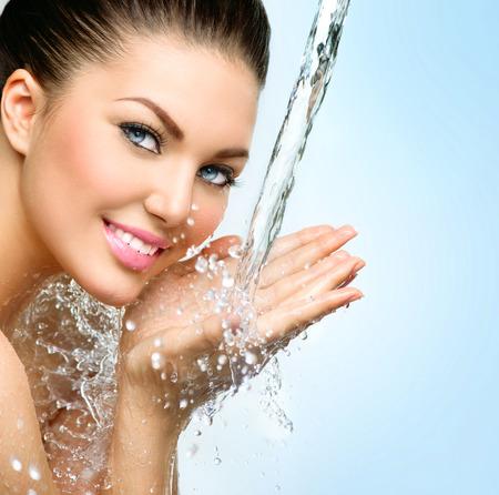 chicas guapas: Hermosa muchacha sonriente bajo un chorrito de agua