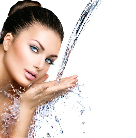 Beautiful model woman with splashes of water in her hands photo