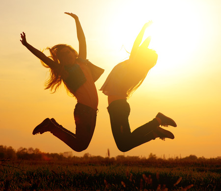 Silhouette of a beautiful girls jumping over sunset photo