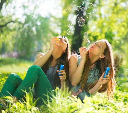うれしそうな 10 代の少女笑いとシャボン玉を吹く 写真素材