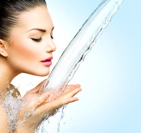 Vacker modell kvinna med stänk av vatten i hennes händer