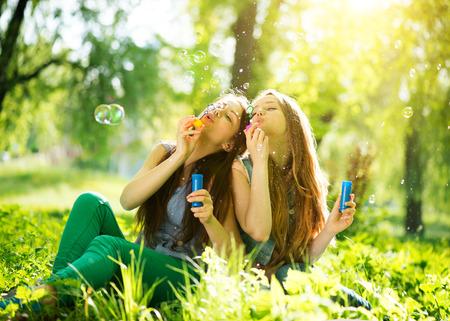 Radostné dospívající dívky se smíchem a foukání mýdlových bublin